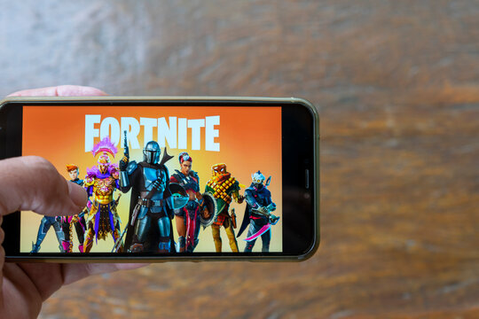 the cell phone in hand with the screen of the Fortnite online multiplayer video game, for smartphone. Space for text.