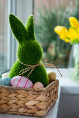 Close up Easter bunny rabbit in straw basket with colored eggs on the windowsill with fresh spring...