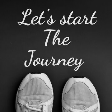Inspirational and motivational quote. Phrase Lets start the journey written on black background with sports shoes.