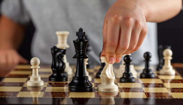 A caucasian boy is holding a white knight chess piece during a game. He will make a move. Dark background image for determination, concentration, focusing, calculation risk taking behavior concepts