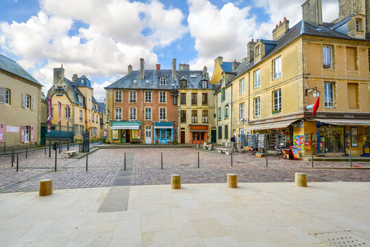 The small square outside the entrance to the Bayeux Cathedral, with colorful shops and cafes in the Normandy town of Bayeux, France.