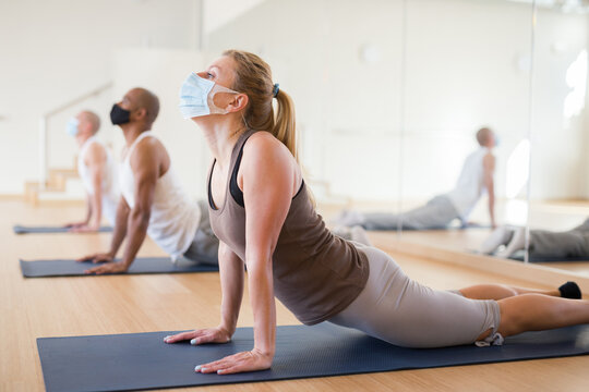 Young adult sporty woman in protective face mask practicing yoga with group at fitness center during coronavirus pandemic