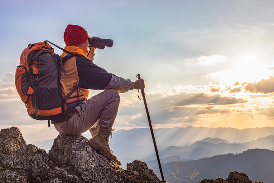 Hikers with backpacks holding binoculars sitting on top of the rock mountain