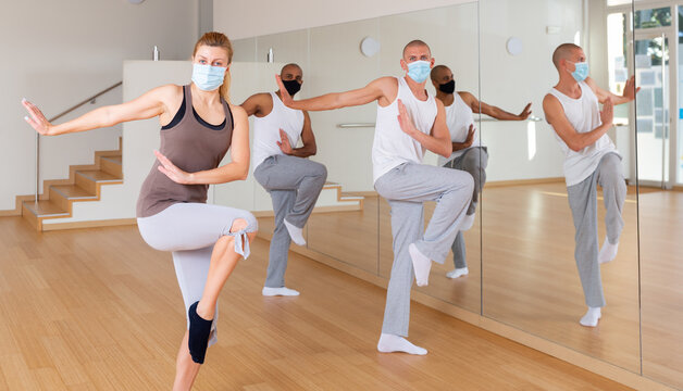 Group of people in protective masks practicing active rhythmic dancing in dance studio. Forced precautions in COVID pandemic