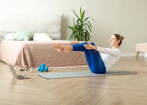 Home yoga online. Adult caucasian woman sit on the floor in boat pose in front of the laptop and catch a balance, selective focus.