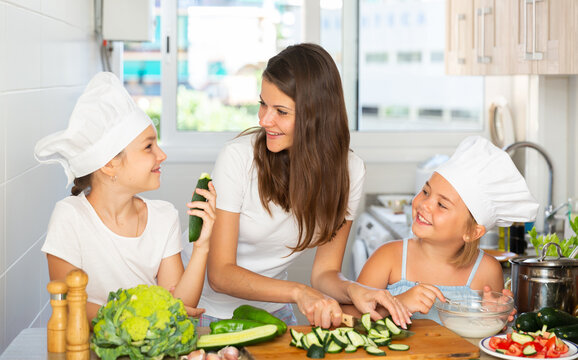 Portrait of single mother with two daughters wearing chef hats cutting vegetables, preparing dinner at home and having fun