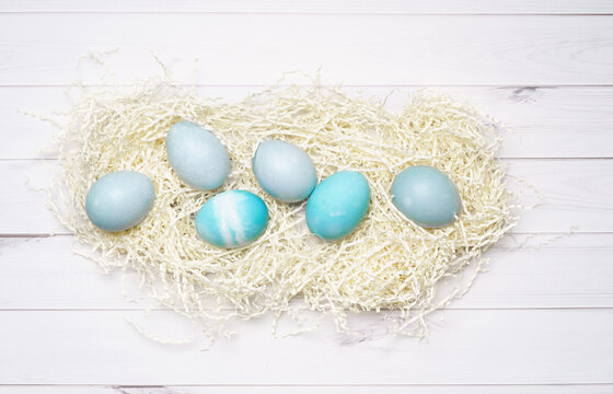 Blue eggs for Easter decor on wood background.