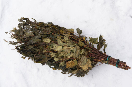 A broom for a bath made of birch branches lies on the snow