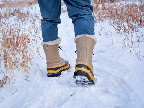 legs of male hiker in heavy snow boots on a trail in northern Colorado at foothills of Rocky Mountains