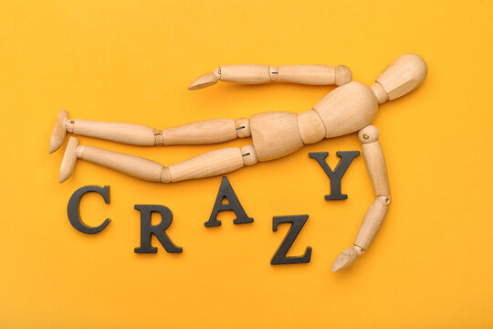 Wooden mannequin with word CRAZY on color background