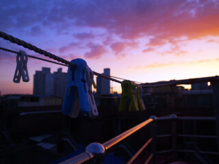 Obraz The sunset over the city as you look at the laundry from the rooftop. - fototapety do salonu