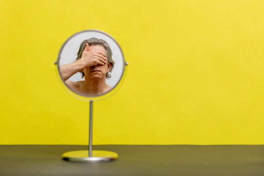 On a yellow background, a round mirror with the reflection of a man covering his face with his hand.