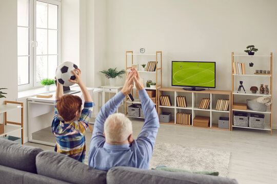 People sitting on sofa at home and enjoying final football match on TV. Granddad and grandchild supporting favorite team while watching soccer on big television set in Scandinavian style living-room