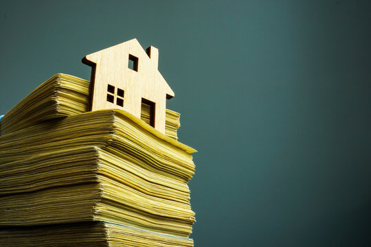 Money for property buying and investment. Small home and stack of cash.