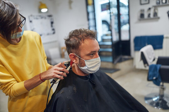 Hairdresser and customer in a salon with medical masks during virus pandemic. Working with safety mask.
