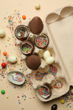 Egg box with chocolate eggs with sprinkles on beige background
