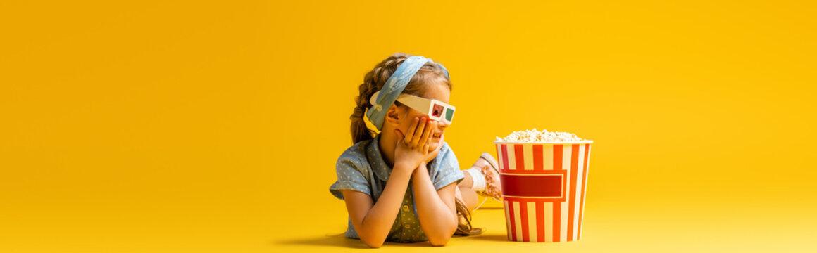 happy kid in 3d glasses lying near popcorn bucket on yellow, banner