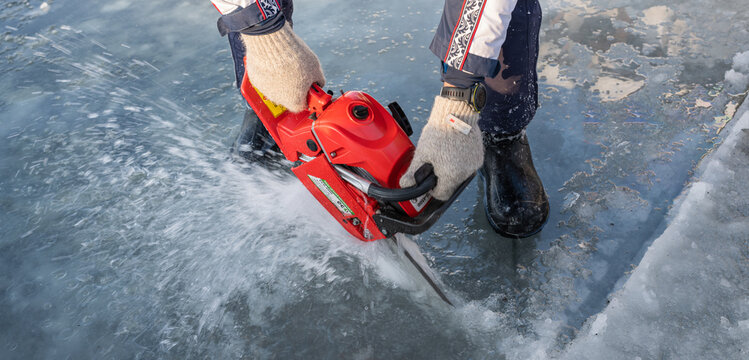 Russia, River Volga Kama - Jan 17th 2020. Man carving an ice hole entry with a motor saw chainsaw for ice scuba diving