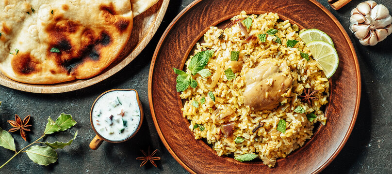 Pakistani food - biryani rice with chicken and raita yoghurt dip. Delicious hyberabadi chicken biryani on dark background. Top view or flat lay. Copy space for text or design. Long horizontal banner