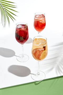Assortment of sangria drinks on white table. Sunshine with hard shadow. Palm leaves and shadow. Fresh, summer, tropic, beach drink concept