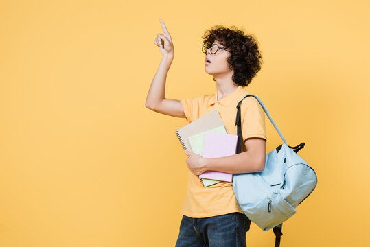 Curly schoolboy with backpack and notebooks pointing with finger isolated on yellow