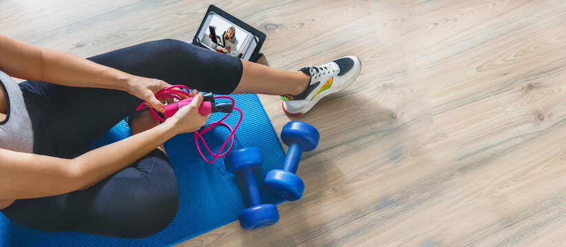 Fitness at home, remote training with virtual instructor. Woman in sportswear sitting on the floor with dumbbells laptop at home. Sports and recreation concept in lockdown with fitness apps online