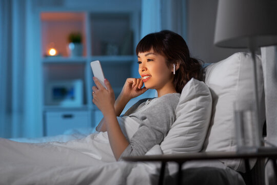 technology, internet and people concept - happy smiling young asian woman with smartphone and wireless earphones lying in bed at home at night