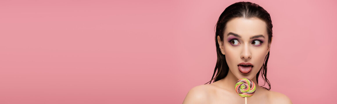 young woman with eye shadows sticking out tongue near lollipop isolated on pink, banner