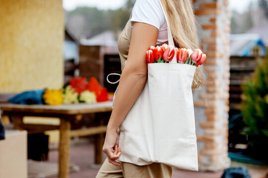 Close-up of a bouquet of tulips in a cloth bag on the shoulder of a girl. Gift for Women's Day, Valentine's Day, Mother's Day