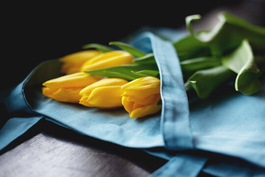 A bouquet of yellow tulips lies on a blue cloth bag, side view. The concept of Women's Day and Valentine's Day