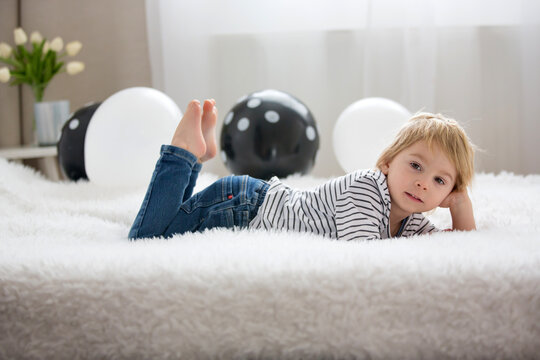 Cute toddler blond child, baby boy, lying in bed with balloons, smiling at camera
