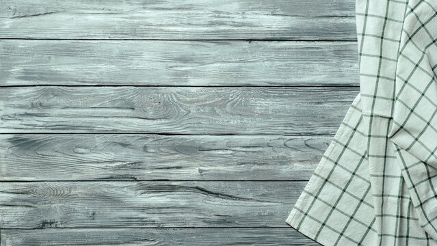 Gray wooden table with linen kitchen towel or textile napkin flat lay. Blue tablecloth on old gray wood tabletop. Copy space for text. Can use as mock up for design.
