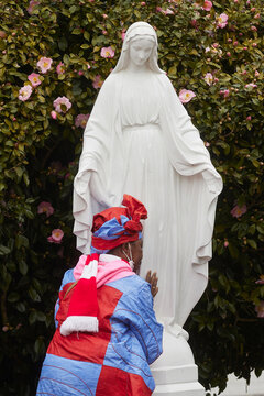 Martha Gendonou prays to a statue of the Virgin Mary after attending mass at Saints Peter and Paul Catholic Church in Atlanta