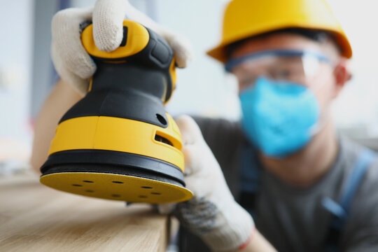 Master builder in protective mask is holding disc sander. Renovation services concept