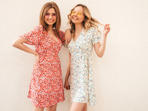 Two young beautiful smiling hipster female in trendy summer sundress.Sexy carefree women posing on the street background in sunglasses. Positive models having fun and going crazy
