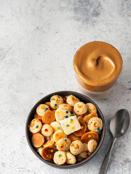 Mini pancakes cereal and dalgona coffee on gray cement background, copy space. Trendy food and drink - tiny panckakes and whipped instant coffee with milk or korean dalgona coffee. Top view. Vertical