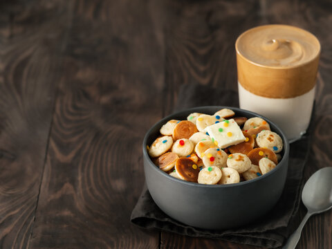 Mini pancakes cereal and dalgona coffee on brown wooden background, copy space. Trendy food and drink - tiny panckakes served sprinkles and whipped instant coffee with milk or korean dalgona coffee
