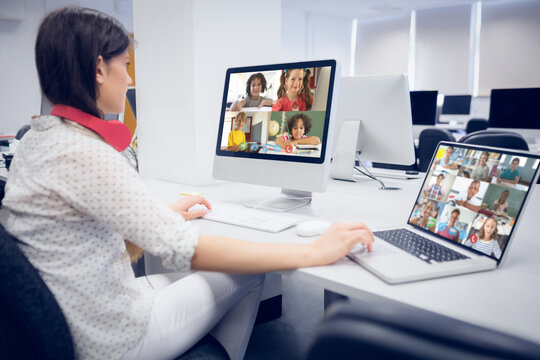 Female teacher wearing headphones having a video call with multiple students at school on laptop and