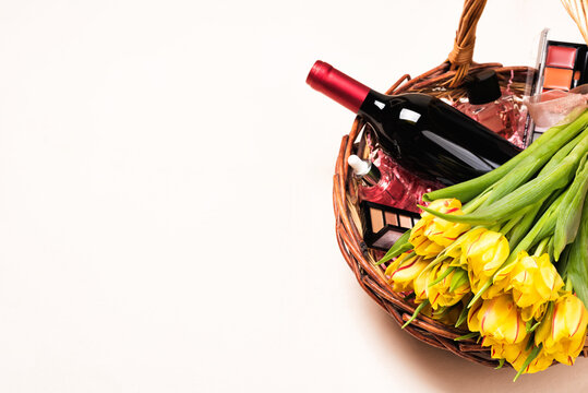 Bottle of red wine, tulip flowers and cosmetic in gift basket for Women's day and month, Mother's Day, birthday