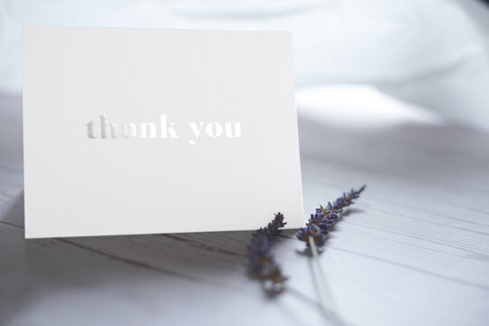 Thank you card  on wooden table with a pair of lavender flowers. Elegant minimalist composition with white background. Special thank you note.