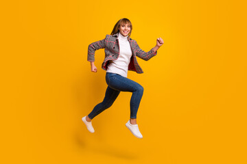 Wall Mural - Full body profile portrait of attractive lady running look camera toothy smile isolated on yellow color background