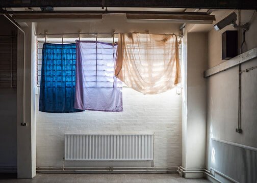 Coloured prisoner bedsheets hanging as curtains over prison bars sunlight in window of high security run down immigration detention centre in England with CCTV security camera monitoring the room