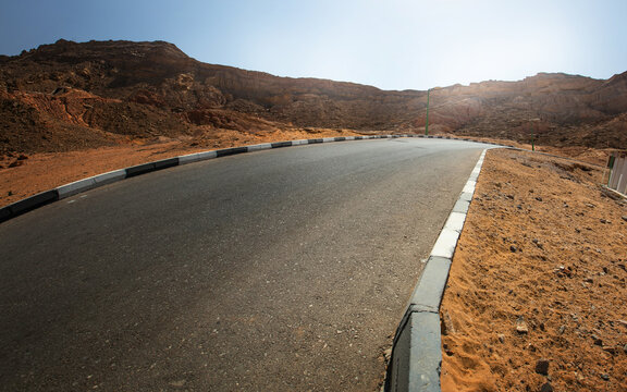 Travel and vacation background. View of the ground and the desert road with the mountains.