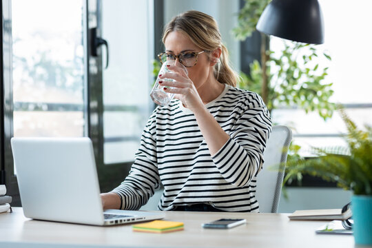 Beautiful mature business woman working with a laptop while drinking glass of water on a desk in the office at home.