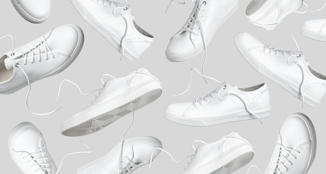 Flying white leather womens sneakers isolated on gray background, different kind. Fashionable stylish sports casual shoes. Creative minimalistic layout with footwear. Advertising for shoe store, blog