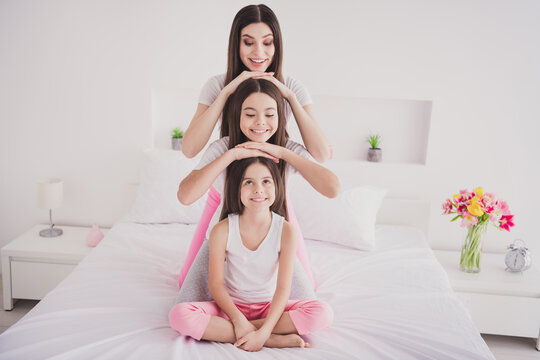 Photo of pretty charming three siblings nightwear sitting bed head pyramid smiling indoors inside room home