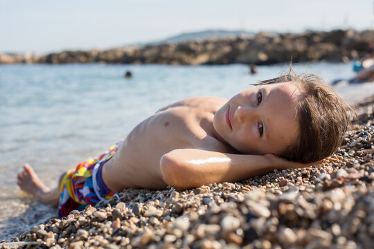 Sweet child, preteen boy, lying on the beach in France on sunset