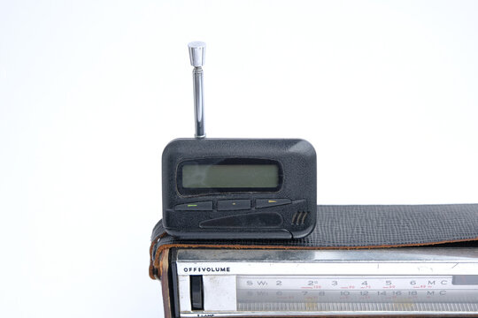 pager, old vintage beeper. the pager lies on an old retro radio with an antenna