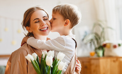tender son kisses the happy mother and gives her a bouquet of tulips, congratulating her on...