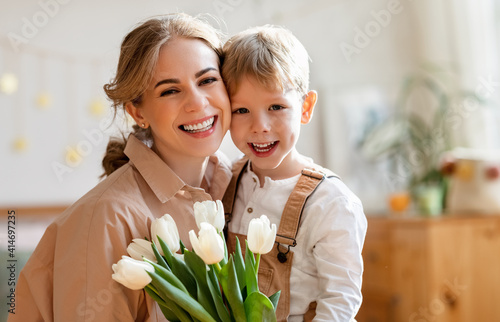 Grateful mother with bouquet hugging son